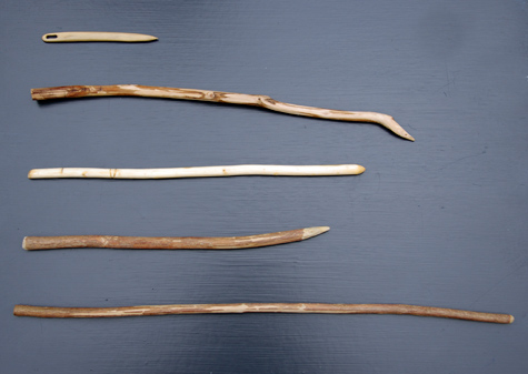 4 whittled wands and a whittled needle