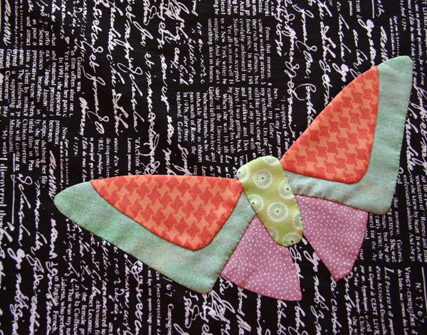 """All A Flutter"" Butterfly ""A"" in bright fabrics on text background."