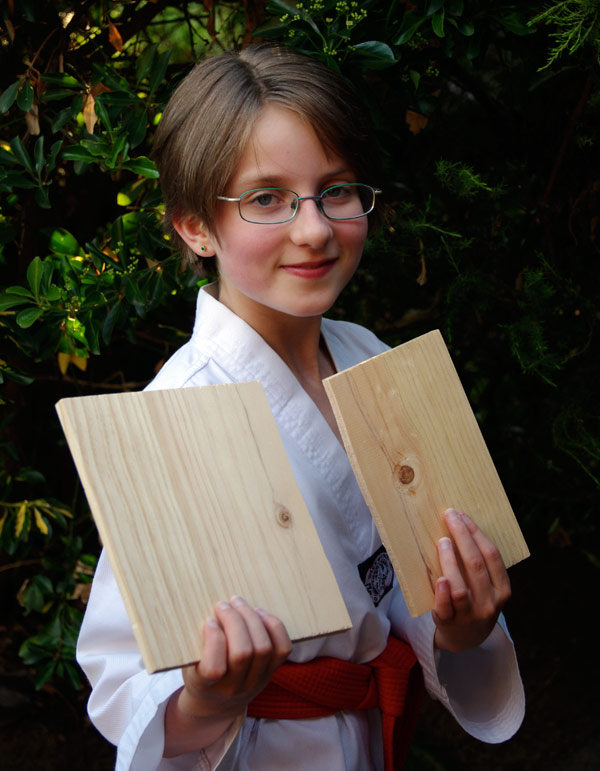 Amelia with the boards she broke at Tawkwondo