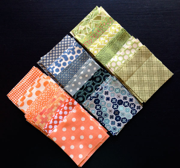 Stack of cut fabric squares in Orange, Blue and Green